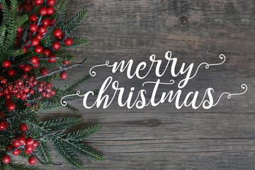Merry Christmas Text With Evergreen Branches And Berries Over Dark Rustic Wood Background
