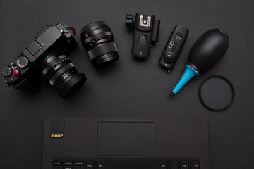 top view of photographer work space with mirrorless camera system, Dust blower, Lens filter, Wireless flash trigger, and SD card on laptop