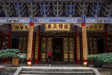 Tourist looking inside elegant red-golden gate in Chinese Buddhist temple