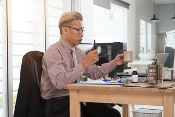 sick asian senior at work