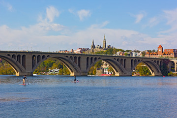 Young couple kayaking on Potomac River on a beautiful autumn afternoon near Key Bridge. Georgetown urban panorama near the water in Washington DC, USA.
