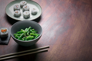 Japanese sushi and green beans on a dark wooden background