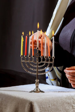 Lighting Menoral Candles man hand lighting candles in menorah on table served for hanukka