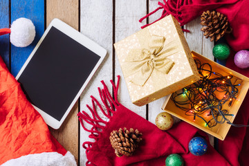 Top view of Tablet and christmas decoration on wooden table.