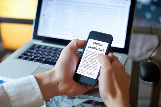 terms and conditions, man reading agreement on the screen of smartphone
