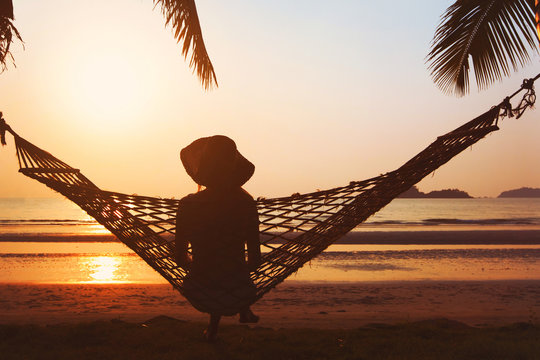 beach holidays, silhouette of woman in hat at sunset in hammock, happy vacation