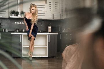Beautiful sexy stand next the table on a kitchen. Portrait of fashion model girl indoors. Beauty blonde woman tries to seduce you. Temptation
