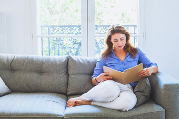 adult education, middle aged woman reading at home