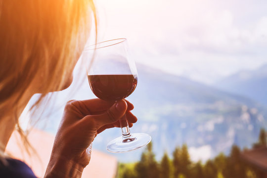 woman drinking red wine, close up of hand holding glass