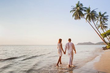romantic young couple walking together on beautiful exotic tropical beach at sunset