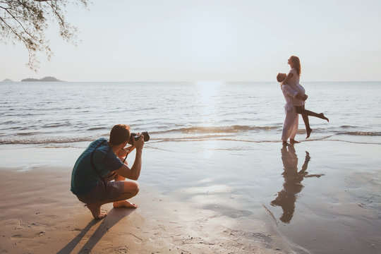 wedding and lifestyle photographer taking photos of affectionate couple on the beach at sunset