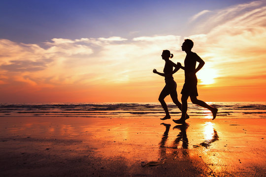 running background, sport and workout, silhouettes of people jogging at sunset beach