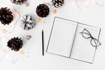 Notebook diary christmas mockup, pine cones and decorations on white background, flat lay top view.