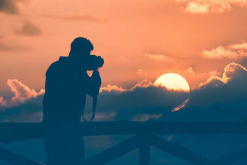 silhouette of man photographer take photos with sunset background
