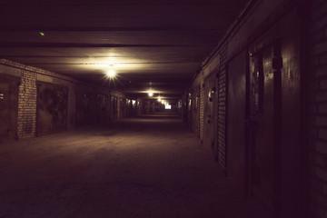 Dark long hallway with metal gates and working bulbs