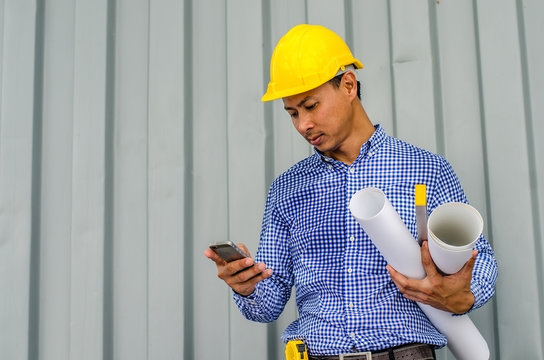 Confident architect. Handsome young man in hardhat holding blueprint and using mobile phone while standing outdoors and against building structure
