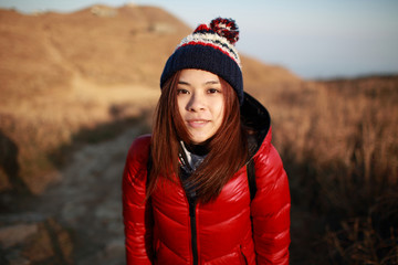 Beautiful sweet Young girl wear the down jacket and hat  Travel in winter view under sunset evening on the mountain landscape countryside background, face close up