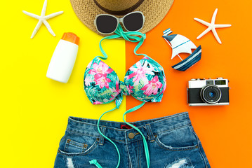 Summer Fashion woman swimsuit Bikini. Tropical travel the sea. Unusual top view, colorful yellow and orange background.  Summer & Travel Concept.