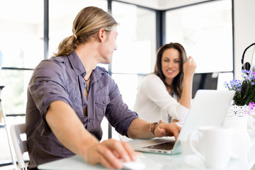 Image of two young business people in office
