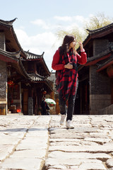 Sight see : chinese travel pretty girl walk on the rock road of historic old town in Lijiang,  Yunnan province with old building background