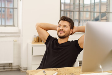 mann sitzt am schreibtisch und lehnt sich zufrieden zurück