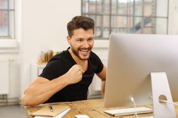 glücklicher mann schaut auf seinen computer und ballt die faust
