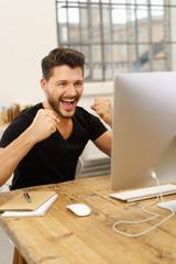mann schaut auf seinen computer und schreit vor glück