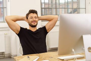 zufriedener junger unternehmer im büro