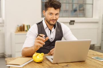 geschäftsmann mit laptop und sparschwein