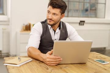 mann arbeitet am notebook und schaut in gedanken zur seite