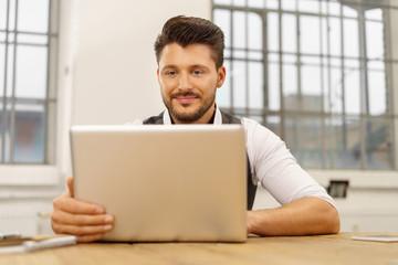 erfolgreicher unternehmer schaut auf seinen laptop