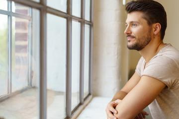 entspannter mann schaut aus dem fenster
