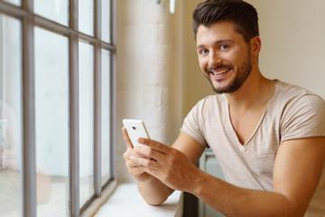 lachender junger mann mit handy steht am fenster