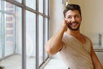 mann telefoniert und schaut lächelnd aus dem fenster