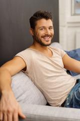 lachender mann sitzt auf einem grauen sofa