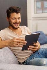 mann sitzt auf dem sofa und schaut auf sein tablet