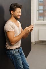 mann schaut lächelnd auf sein mobiltelefon