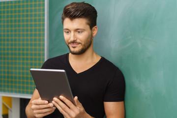 lehrer nutzt sein tablet im unterricht