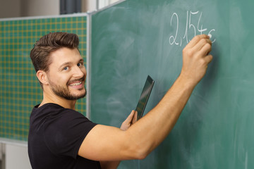 lehrer schreibt an die tafel und hält sein tablet-pc in der hand