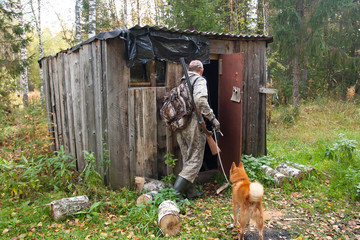hunter with dog near the forest hut
