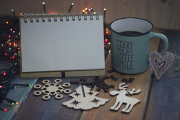 A blue cup of coffee or cappuccino, an open notebook, a wooden snowflake, a deer and an angel, a heart-shaped carrot on a table in a country house for Christmas, a top view
