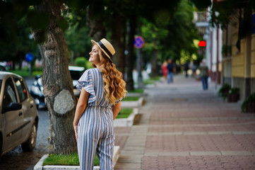 Portrait of a very attractive young woman in striped overall posing with her hat on a pavement in a town with trees in a background.