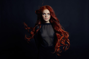 Portrait of redhead sexy woman with long hair on black background. Perfect girl with the blue eyes, nice clean skin, beautiful natural makeup, red hair