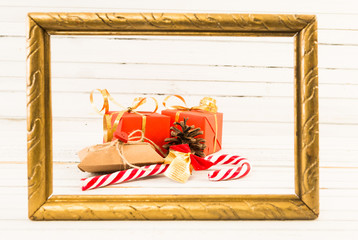 Wrapped gifts or presents and cane candy on golden photo frame