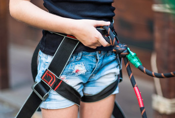 Girl wearing safety harness on her belt in rope park. Close-up image.