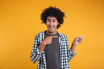 Portrait of a cheerful young african man pointing fingers away