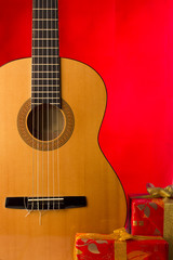 Guitar and holiday boxes on Red christmas background