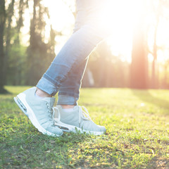 Stepping in blue jeans and comfortable gray shoes good for running, standing in sunlight