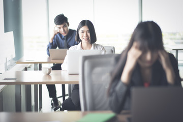 Young Business woman working at laptop as desks in modern office surrounded by colleagues are stresse , Business Concept