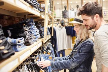 Junges Paar im Jeans Mode Shop beim Einkaufen